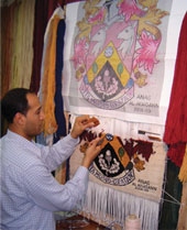 Anas hand-weaving rug knots on the Haslemere Coat of Arms Weavin